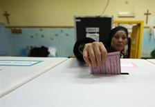 Los italianos comenzaron el domingo a votar en unas de las elecciones que serán seguidas más de cerca de los últimos años, con los mercados nerviosos por si saldrá un gobierno fuerte que saque a Italia de la recesión y ayude a resolver la crisis de deuda de la eurozona. En la imagen, una monja deposita su voto en un centro electoral de Roma, el 24 de febrero de 2013. REUTERS/Yara Nardi