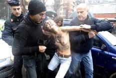 La policía se llevó por la fuerza el domingo a un grupo de mujeres en topless que protestaban contra el ex primer ministro Silvio Berlusconi mientras votaba en las elecciones de Italia. En la imagen, de 24 de febrero, una de las activistas del grupo Femen detenidas por la policía tras protestar contra Berlusconi en las elecciones de Italia. REUTERS/Cezaro De Luca