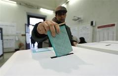 Un uomo inserisce una scheda elettorale nell'urna a Roma, 24 febbario 2013. REUTERS/Yara Nardi
