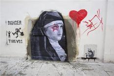 Dos murales pintados con spray por el evasivo artista callejero Banksy, incluyendo uno que desapareció la semana pasada de una calle del norte de Londres, se retiraron de una subasta en Miami el sábado. En la imagen, de 23 de febrero, la imagen de una virgen y un corazón pintados en la pared de donde extrajo uno de los murales de Banksy en las calles de Londres. REUTERS/Neil Hall