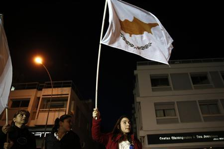 Supporters of conservative Cyprus Presidential candidate Nicos Anastasiades wave the national flag as they celebrate outside a pre-election campaign bureau in Nicosia February 24, 2013. REUTERS/Yorgos Karahalis