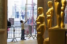 """Menino aponta para estátuas de Oscars no tapete vermelho durante preparativos para a 85a edição da premiação em Hollywood, EUA. O Oscar estende o tapete vermelho no domingo para a maior noite da indústria do cinema, com o drama dos reféns do Irã """"Argo"""" e o drama presidencial """"Lincoln"""" em uma disputa acirrada pelo título de Melhor Filme. 23/02/2013 REUTERS/Lucas Jackson"""