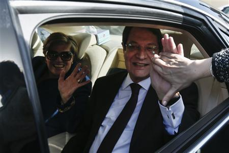 Cyprus presidential candidate Nicos Anastasiades, of the right wing Democratic Rally party (R), and his wife Andriana greet supporters as they leave a polling station in Limassol February 24, 2013. REUTERS/Yorgos Karahalis