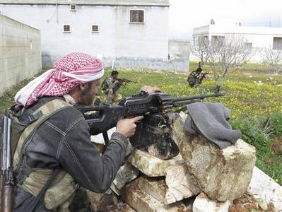 Free Syrian Army fighters hold their weapons and take positions in preparation for what they say is an ambush against forces loyal to Syria's President Bashar al-Assad in Binnish in Idlib Province February 21, 2013. REUTERS/Mohamed Kaddoor/Shaam News Network/Handout