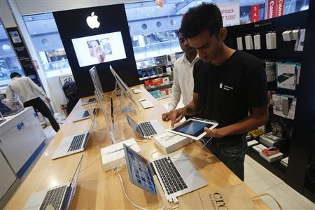 A salesperson unpacks an Apple iPad Mini to test it for a customer in the Apple specialty section of a Croma retail store in Mumbai February 22, 2013. REUTERS/Vivek Prakash