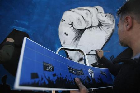 A member of ''Damn the Troika'' movement works on a mural in Lisbon February 24, 2013. REUTERS/Rafael Marchante