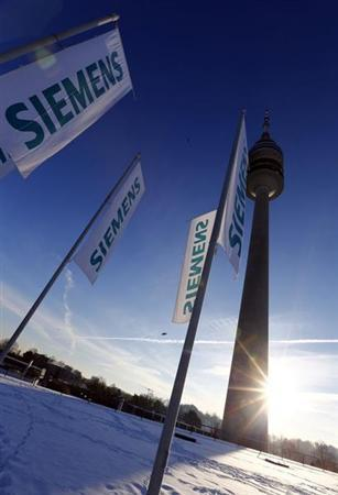 Flags of German engineering conglomerate Siemens AG flutter before the company's annual shareholder meeting in Munich January 23, 2013. REUTERS/Michael Dalder