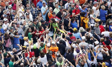 NASCAR driver Danica Patrick greets fans before the start of the NASCAR Sprint Cup Series Daytona 500 race at the Daytona International Speedway in Daytona Beach, Florida February 24, 2013. REUTERS/Pierre Ducharme
