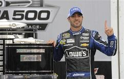 Jimmie Johnson poses next to the trophy after he won the NASCAR Sprint Cup Series Daytona 500 race at the Daytona International Speedway in Daytona Beach, Florida February 24, 2013. REUTERS/Brian Blanco