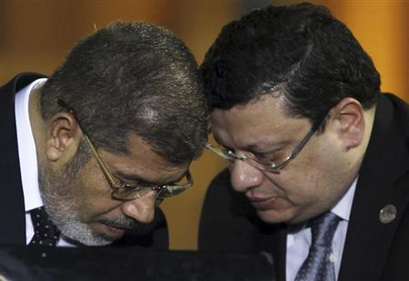 Egyptian President Mohamed Mursi (L) speaks with his media spokesman Yasser Ali during a news conference with Turkish President Abdullah Gul (not pictured) after their meeting at the Presidential Palace in Cairo February 7, 2013. REUTERS/Amr Abdallah Dalsh