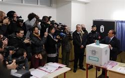 Former Prime Minister Silvio Berlusconi casts his vote at a polling station in Milan February 24, 2013. Italians began voting on Sunday in one of the most closely watched elections in years, with markets nervous about whether it can produce a strong government to pull Italy out of recession and help resolve the euro zone debt crisis. REUTERS/Stefano Rellandini (ITALY - Tags: POLITICS ELECTIONS BUSINESS)
