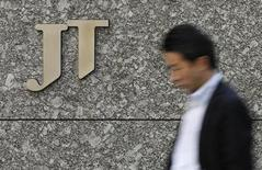 A man walks past a logo of Japan Tobacco Inc (JT) outside the company's headquarters building in Tokyo February 20, 2013. REUTERS/Toru Hanai