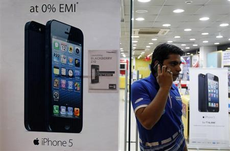 A man speaks on his mobile phone while standing next to posters advertising an Apple iPhone 5 and Blackberry Z10 in Ahmedabad February 22, 2013. REUTERS/Amit Dave