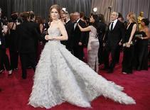 """Etéreos, escotes palabra de honor y tirabuzones dieron el domingo una pátina del glamour antiguo de Hollywood a la alfombra roja de los Oscar a medida que las principales actrices y presentadoras se abrieron camino con vestidos de lentejuelas pálidos, grises y negros. En la imagen, de 24 de febrero, Amy Adams, nominada a mejor actriz de reparto por """"El Master"""", una de las mejores vestidas en la alfombra roja de los Oscar, con un diseño de Óscar de la Renta. REUTERS/Lucy Nicholson"""