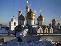 Мужчина убирает снег около храма в Москве, 27 января 2012 года. Москвичей ждет небольшое потепление на рабочей неделе, прогнозируют синоптики. REUTERS/Anton Golubev