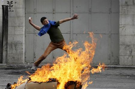 A Palestinian protester throws a stone during clashes with Israeli soldiers and border policemen in the West Bank city of Hebron February 24, 2013. REUTERS/Ammar Awad