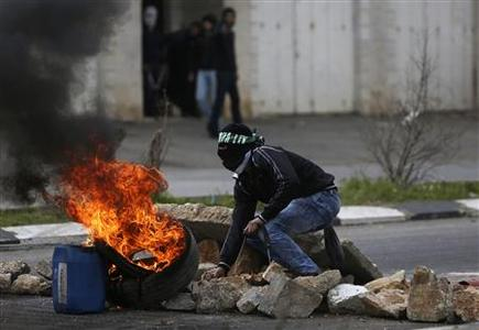 A stone-throwing Palestinian protester crouches near burning tyres during clashes with Israeli soldiers and border policemen outside Israel's Ofer military prison near the West Bank city of Ramallah February 24, 2013. Israel on Sunday demanded the Palestinian Authority stem a surge of anti-Israeli protests ahead of U.S. President Barack Obama's visit to the region next month. The death in an Israeli jail of a Palestinian detainee on Saturday and an on-going hunger strike by four inmates have fuelled tensions in the West Bank. REUTERS/Mohamad Torokman