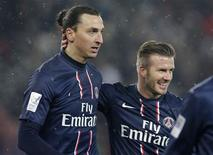 El ex capitán de Inglaterra David Beckham disfrutó de un prometedor debut en la liga francesa con el Paris St Germain, recibiendo el calor de los aficionados en una breve aparición en la victoria del domingo por 2-0 en casa contra el Marsella. En la imagen, de 24 de febrero, David Beckham felicita a Zlatan Ibrahimovic tras su gol contra el Olympique de Marsella en su debut con el PSG en la Ligue 1. REUTERS/Gonzalo Fuentes