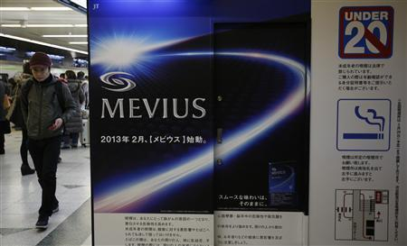 People walk past an advertisement of Mevius, one of Japan Tobacco's brands, at a kiosk in Tokyo February 20, 2013. REUTERS/Yuya Shino