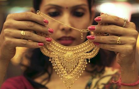 A salesgirl shows a gold necklace to customers at a jewellery showroom in of Chandigarh November 11, 2012. REUTERS/Ajay Verma/Files
