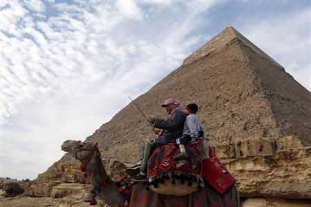 A man and a boy ride a camel as they wait for tourists in front of a part of the Giza pyramid, near Cairo January 12, 2013. REUTERS/Asmaa Waguih