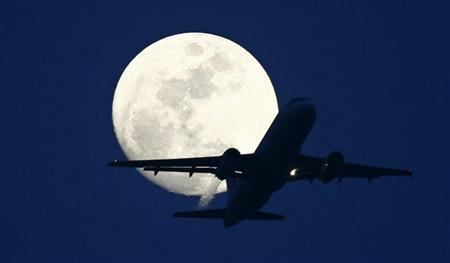 A passenger aircraft is silhouetted against the rising moon in New Delhi May 7, 2009. REUTERS/B Mathur