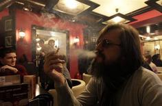 El presidente de Rusia, Vladimir Putin, ha firmado una ley que prohibirá fumar en la mayoría de lugares públicos y restringirá las ventas de cigarrillos en el segundo gran mercado de tabaco mundial después de China. En la imagen, tomada el 24 de enero, un hombre fuma un cigarrillo en un café de Krasnoyarsk en Siberia. REUTERS/Ilya Naymushin