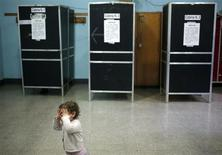 A child covers her face as she waits for her mother voting at a polling station in Rome February 24, 2013. Italians began voting on Sunday in one of the most closely watched elections in years, with markets nervous about whether it can produce a strong government to pull Italy out of recession and help resolve the euro zone debt crisis. REUTERS/Yara Nardi (ITALY - Tags: POLITICS ELECTIONS) ATTENTION EDITORS - ITALIAN LAW REQUIRES THAT THE FACES OF MINORS ARE MASKED IN PUBLICATIONS WITHIN ITALY