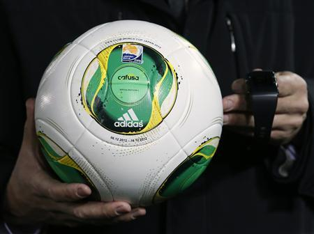 Ingmar Bretz, GoalRef Sports Technology Programme Manager, holds a ball and wrist watch for a goal-line technology system by the FIFA-selected provider GoalRef, which will be used at the Club World Cup football tournament, at the Yokohama International Stadium in Yokohama, south of Tokyo December 5, 2012. REUTERS/Toru Hanai