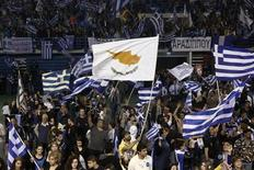 A supporter of the newly elected President of Cyprus Nicos Anastasiades waves a Cypriot flag amongst Greek ones during a proclamation ceremony at Eleftheria stadium in Nicosia February 24, 2013. Cypriot conservative leader Nicos Anastasiades won an overwhelming victory in a presidential run-off election on Sunday, boosting hopes of a swift financial rescue for the near-bankrupt island nation. REUTERS/Yorgos Karahalis (CYPRUS - Tags: POLITICS ELECTIONS)