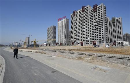 A resident walks past a construction site of a residential compound in Taiyuan, Shanxi province, February 22, 2013. China's new home prices rose an average of 0.8 percent in January from a year earlier, snapping 10 months of decline and raising the risk Beijing may seek to bolster a three-year campaign to curb property inflation. REUTERS/Jon Woo (CHINA - Tags: BUSINESS CONSTRUCTION REAL ESTATE)