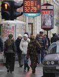Люди проходят мимо вывески пункта обмена валюты в Санкт-Петербурге 13 января 2009 года. Рубль стабилизировался на дневных торгах понедельника к бивалютной корзине и не стал продолжать утренний рост: экспортеры не показали больших объемов продажи валютной выручки под уплату НДПИ, также их может не устраивать текущее ослабление доллара на глобальный рынках. REUTERS/Alexander Demianchuk