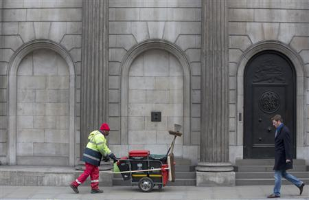 A street cleaner and a pedestrian walk past the Bank of England in the City of London February 23, 2013. REUTERS/Neil Hall