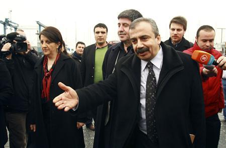 Pro-Kurdish politicians Sirri Sureyya Onder (R), Pelvin Buldan (L) and Altan Tan (C), are surrounded by media members before leaving for Imrali island in Istanbul February 23, 2013. REUTERS/Stringer