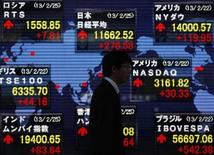 A man walks past a stock index board showing various countries' stock price index outside a brokerage in Tokyo February 25, 2013. The Nikkei average soared 2.4 percent to a 53-month high on Monday with exporters leading gains on a weaker yen, after sources said Japan was likely to nominate Asian Development Bank President Haruhiko Kuroda, an advocate of aggressive monetary easing, as its next central bank governor. REUTERS/Yuya Shino (JAPAN - Tags: BUSINESS)