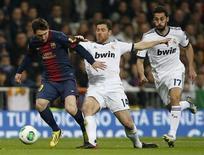 El Real Madrid podrá contar el martes con el centrocampista Xabi Alonso y el delantero Karim Benzema, ya recuperados de lesiones menores, para el partido de vuelta de semifinales de la Copa del Rey contra el Barcelona, el actual campeón, dijo el lunes su entrenador Jose Mourinho. En la imagen de archivo, el jugador del Barcelona Lionel Messi (izquierda), es perseguido por los jugadores del Real Madrid Xabi Alonso y Álvaro Arbeloa (derecha) durante el partido de ida de semifinales de la Copa del Rey en el estadio Santiago Bernabeu, en Madrid, el 30 de enero de 2013. REUTERS/Sergio Perez