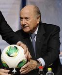 La FIFA ha aprobado y concedido licencia para un tercer sistema para la línea de gol, haciéndolo elegible para su utilización en el Mundial de Brasil 2014, dijo el organismo el lunes en un comunicado. En la imagen de archivo, el presidente de la FIFA Joseph Blatter sostiene un balón de uno de los sistemas de línea de gol durante una rueda de prensa del comité ejecutivo del organismo en Tokio, el 15 de diciembre de 2012. REUTERS/Toru Hanai