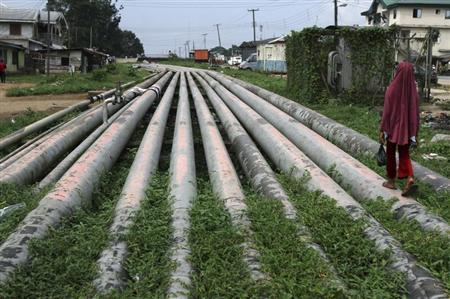 A girl walks on a gas pipeline running through Okrika community near Nigeria's oil hub city of Port Harcourt December 4, 2012. REUTERS/Akintunde Akinleye