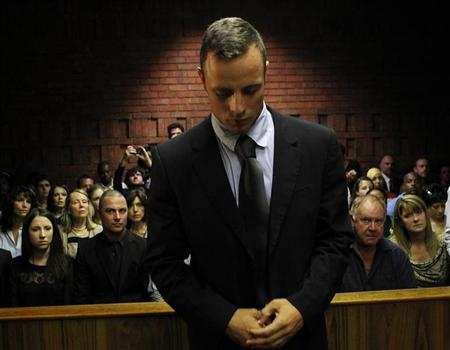 Oscar Pistorius stands in the dock ahead of court proceedings at the Pretoria magistrates court February 22, 2013. REUTERS/Siphiwe Sibeko