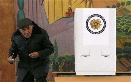 A man holds his ballot before voting at a polling station during the presidential election in Yerevan, February 18, 2013. REUTERS/David Mdzinarishvili