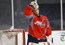 Washington Capitals goalie Braden Holtby puts on his mask as he works out at the team's facility in Arlington, Virginia January 8, 2013.REUTERS/Kevin Lamarque