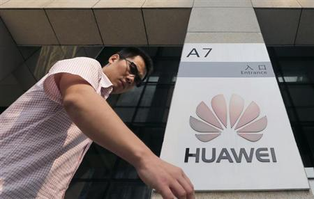 A man walks past a Huawei company logo outside the entrance of a Huawei office in Wuhan, Hubei province, October 9, 2012. REUTERS/Stringer/Files