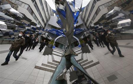 Passers-by are reflected on a decoration at the entrance of a train station in Tokyo February 20, 2013. REUTERS/Yuya Shino
