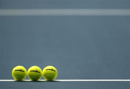 Tennis balls sit on the court before a match at the Australian Open, January 18, 2008. REUTERS/Petar Kujundzic