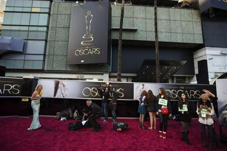 Journalists and stand ins gather on the red carpet outside the Dolby Theatre during Oscar preparations for the 85th Academy Awards in Hollywood, California February 23, 2013. REUTERS/Lucas Jackson