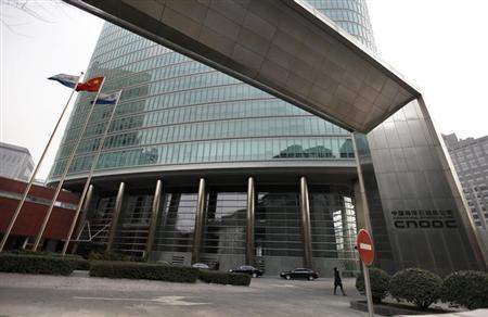 A woman walks out of China National Offshore Oil Corp (CNOOC) headquarters building in Beijing December 10, 2012. REUTERS/Jason Lee/Files