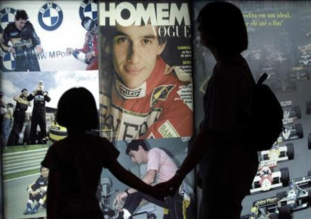 Visitors look at pictures of Brazilian Formula One driver Ayrton Senna displayed at the ''Ayrton Senna Trajectory'' exhibition in Sao Paulo, May 1, 2001. Three time Formula One World Championship Senna was killed in a car accident May 1, 1996, during the Grand Prix of Imola. - RTXKGOZ