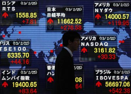 A man walks past a stock index board showing various countries' stock price index outside a brokerage in Tokyo February 25, 2013. REUTERS/Yuya Shino