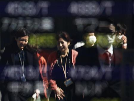 Passers-by are reflected on a window displaying a stock index outside a brokerage in Tokyo February 25, 2013. REUTERS/Yuya Shino