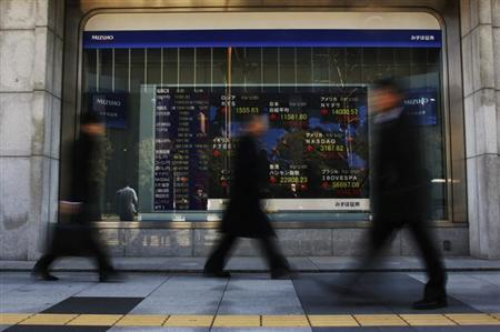 People walk past a stock index board outside a brokerage in Tokyo February 25, 2013. REUTERS/Yuya Shino